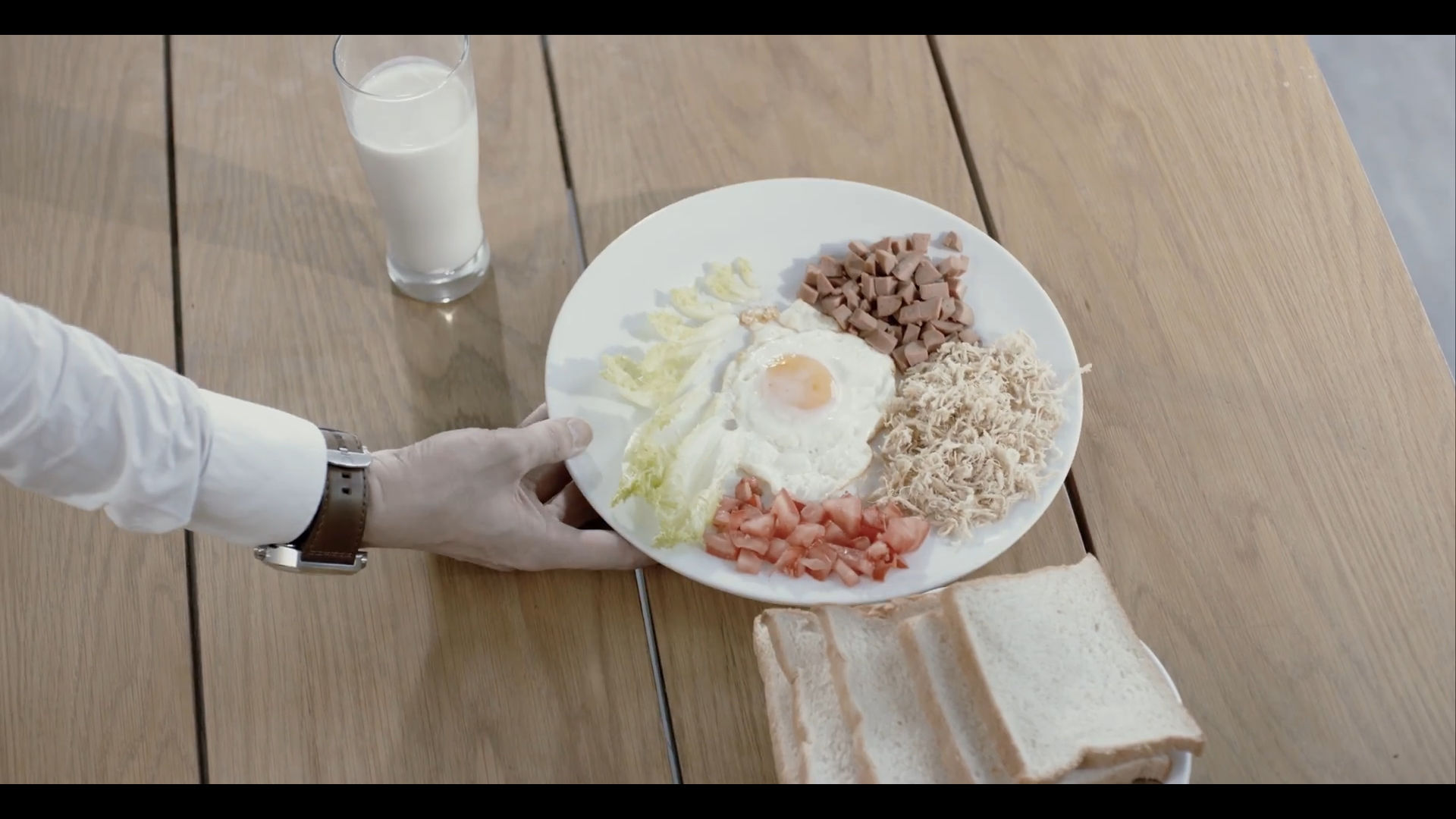 Hot dogs, shredded poultry, diced tomatoes, lettuce, a sunny-side up egg, untoasted white bread, and milk